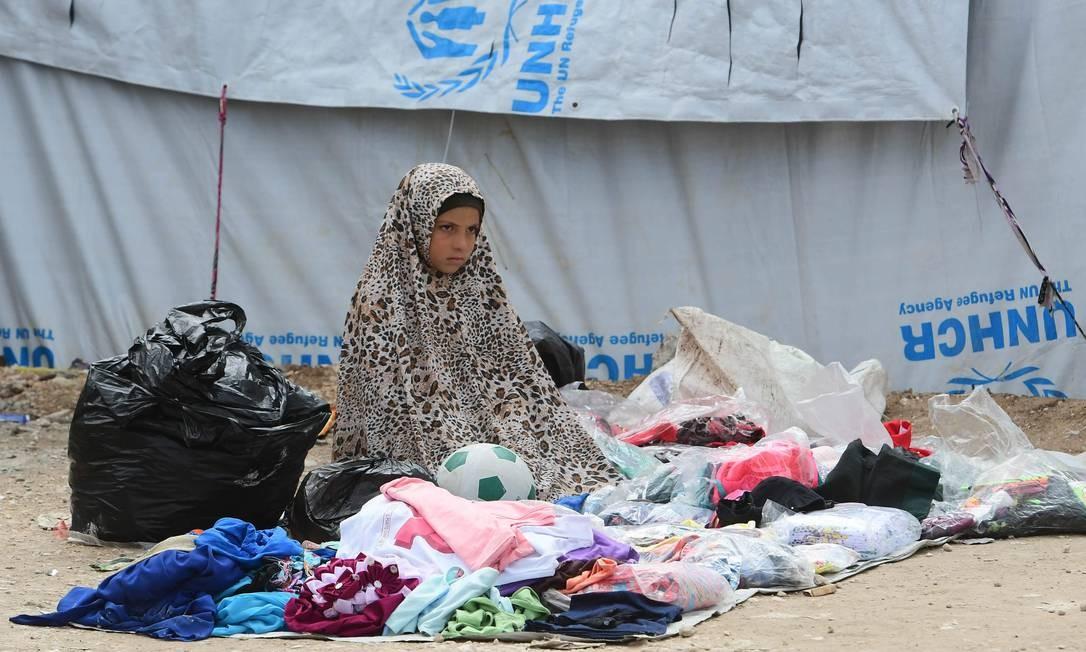 Meninas deslocadas vendem roupas em mercado dentro de campo no norte da Síria; este campo tem mais de 70 mil pessoas hoje, embora tenha sido desenhado para abrigar apenas 10 mil Foto: GIUSEPPE CACACE / AFP