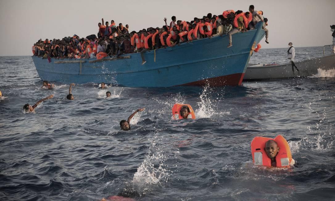 Migrantes, majoritariamente vindos da Eritreia, pulam na água de embarcação clandestina lotada durante resgate no Mediterrâneo Foto: Emilio Morenatti / AP