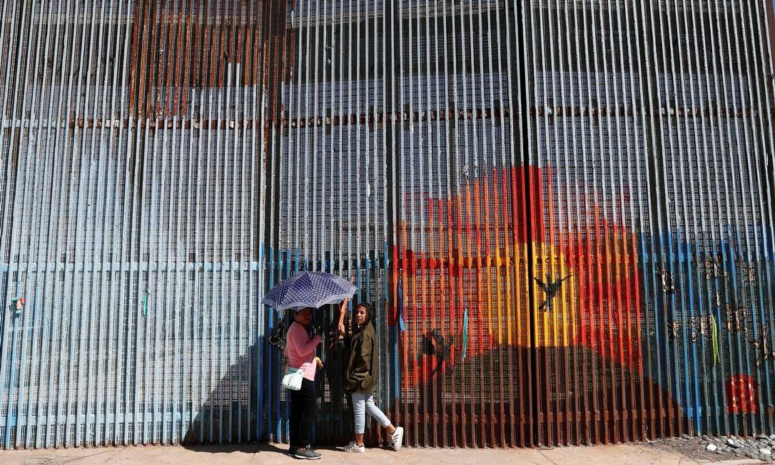 Mulheres vão à cerca que separa México e Estados Unidos para conversar com seus parentes que já cruzaram para o lado americano Foto: CARLOS JASSO / REUTERS