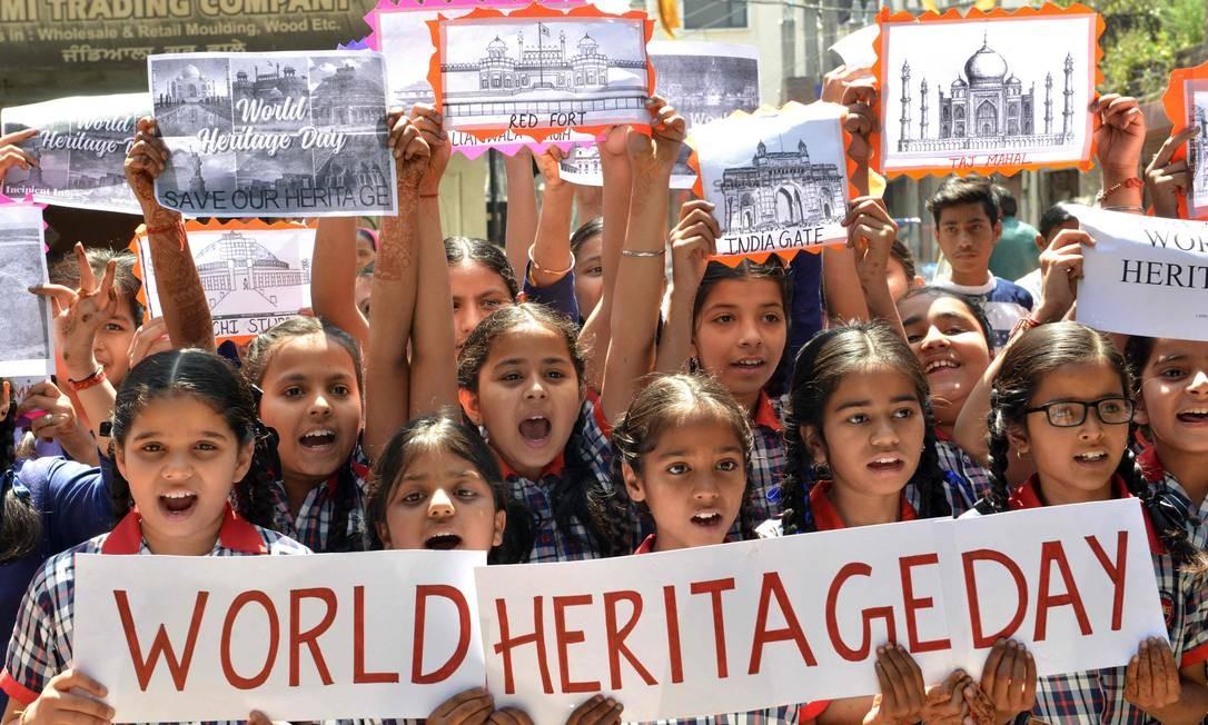 Garotas de escolas indianas seguram cartazes ao comemorar o Dia do Patrimônio Mundial, em Amritsar. O Dia do Patrimônio Mundial, também conhecido como o Dia de Monumentos e Lugares, é celebrado internacionalmente todos os anos no dia 18 de abril com atividades diferentes em monumentos e patrimônios históricos e culturais Foto: NARINDER NANU / AFP