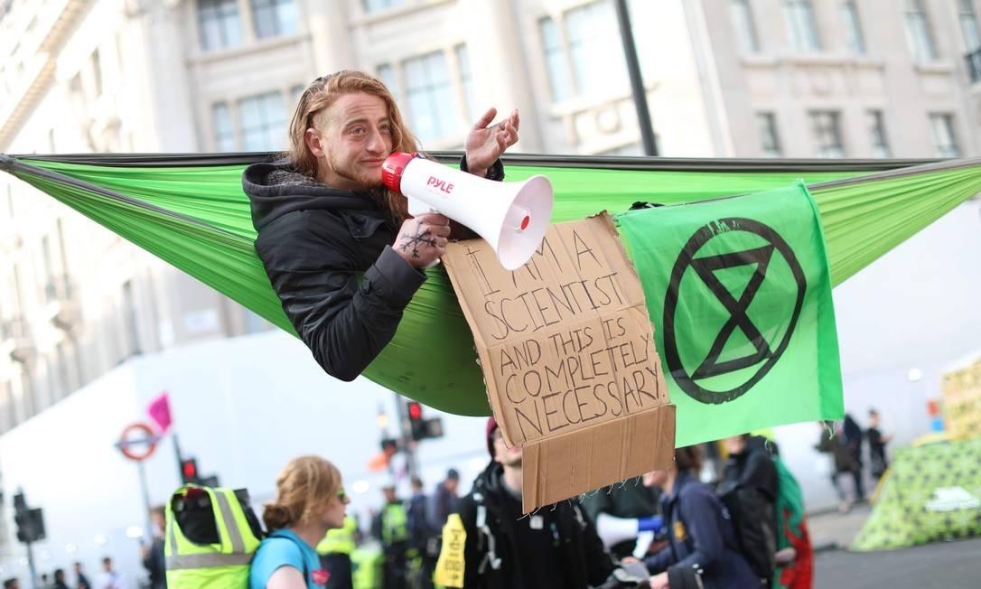 Ativista em uma rede usa um megafone durante protesto sobre mudança climática em Oxford Circus, no movimentado distrito comercial do centro de Londres. Esta quinta-feira (18) marca o quarto dia de um protesto ambiental do grupo Rebelião à Extinção. Quase 300 pessoas foram presas em protestos em andamento em Londres, que paralisaram partes da capital britânica, segundo a polícia local Foto: ISABEL INFANTES / AFP