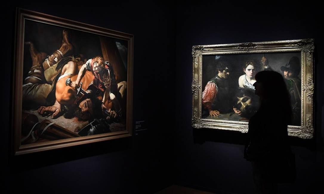 """Os quadros """"Davi com a cabeça de Golias e dois soldados"""", à esquerda, de Valentin de Boulogne, e """"Davi e Golias"""", de Orazio Borgianni, à direita, são mais dois exemplos de obra inspiradas pelo estilo de Caravaggio, presentes na exposição Foto: CHRISTOF STACHE / AFP"""