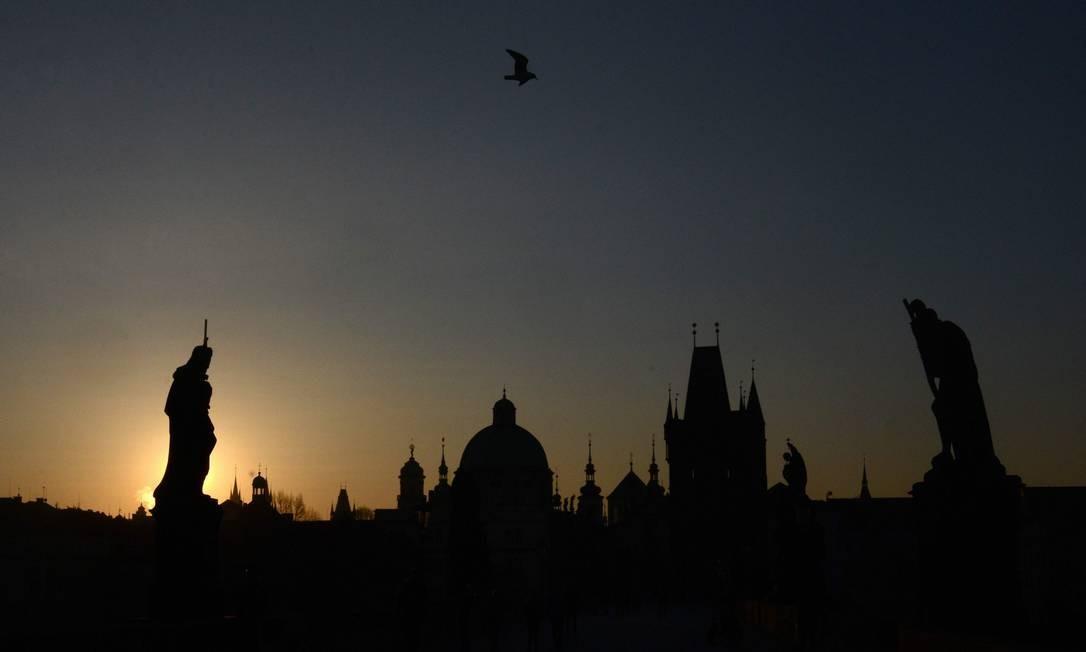 Uma foto tirada ao amanhecer mostra as silhuetas de estátuas e prédios no marco Charles Bridge, em Praga Foto: MICHAL CIZEK / AFP