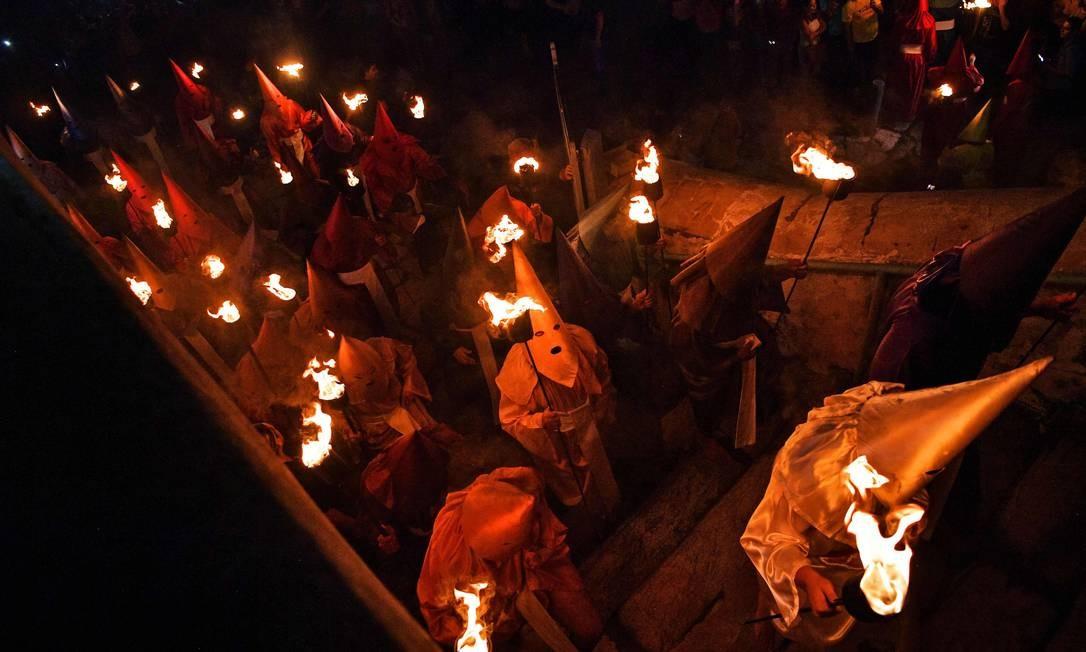 """TOPSHOT - Fiéis católicos vestidos com capuz que representam soldados romanos, conhecidos como """"Farricocos"""", carregam suas tochas durante a tradicional procissão do Fogaréu, festividade católica que acontece anualmente durante a Semana Santa na cidade de Goiás Foto: CARL DE SOUZA / AFP"""