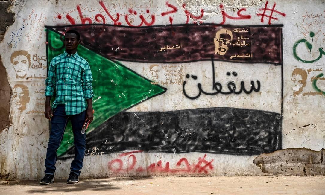Manifestante sudanês diante de um grafite durante em um protesto em frente ao complexo do exército na capital Cartum Foto: OZAN KOSE / AFP
