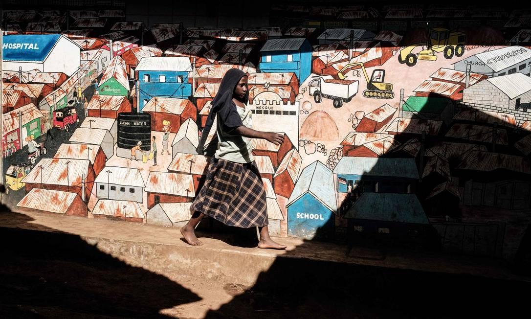 Uma mulher passa por pichações desenhadas na parede da favela de Kibera, em Nairobi Foto: YASUYOSHI CHIBA / AFP