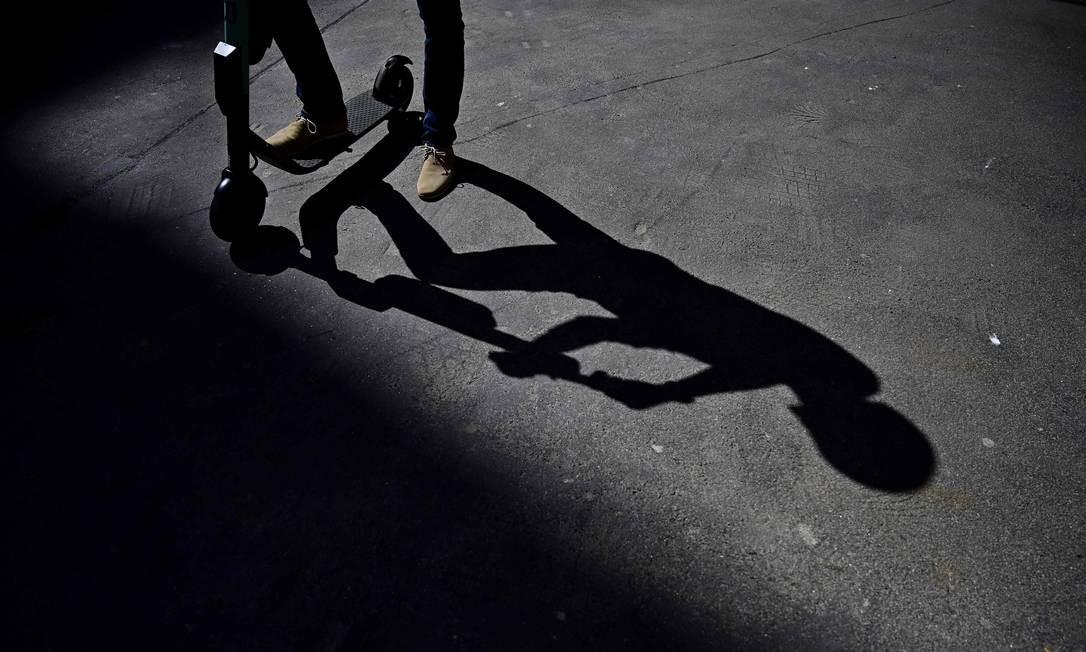 Um homem tem sua sombra projetada enquanto utiliza um patinete por uma rua de Berlim Foto: TOBIAS SCHWARZ / AFP