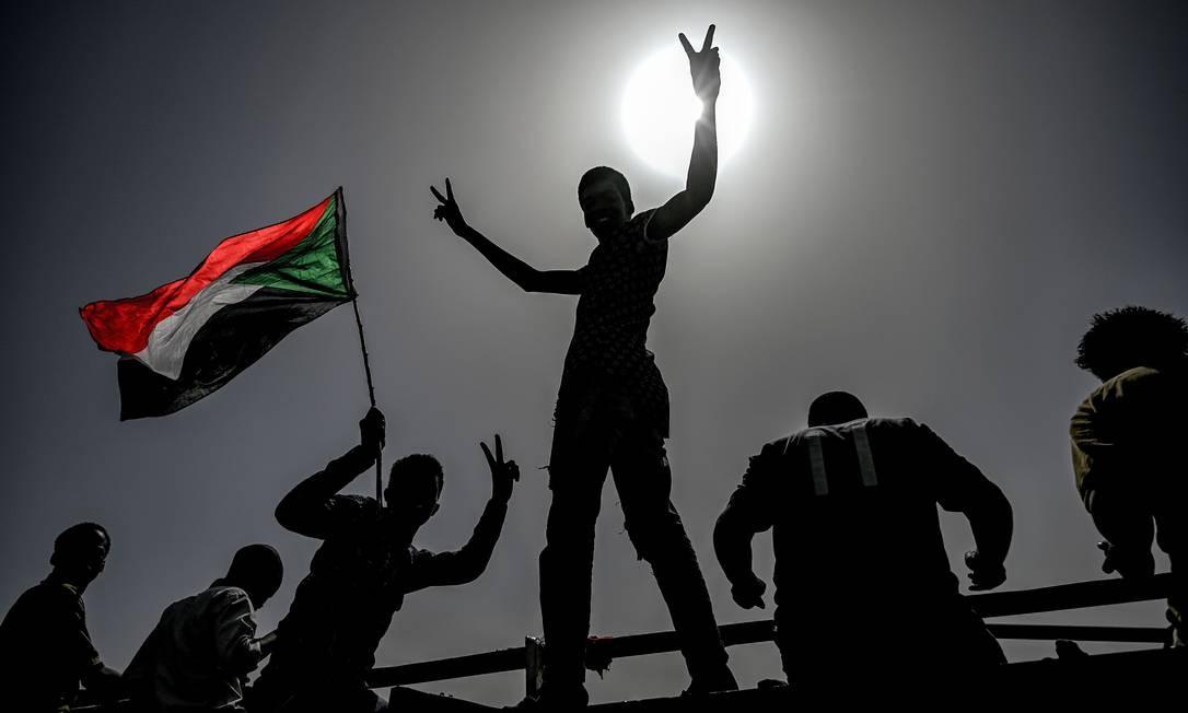 Manifestantes sudaneses acenam bandeiras e fazem sinal de vitória com as mãos enquanto continuam a protestar do lado de fora do complexo militar na capital Cartum, em 17 de abril de 2019. Os manifestantes sudaneses endureceram sua exigência, requerindo que os militares no poder rapidamente renunciassem e abrissem caminho para o governo civil, recusando mover-se da frente do quartel-general do Exército Foto: OZAN KOSE / AFP