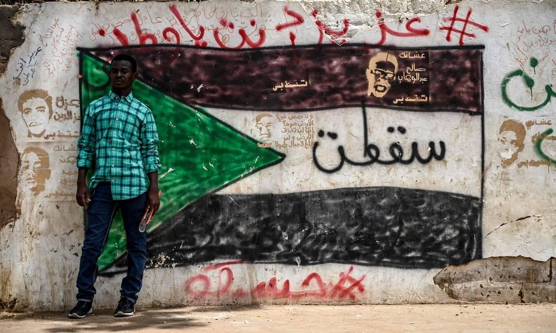 Manifestante sudanês se posiciona em frente a um grafite com a bandeira do país, do lado de fora do complexo do Exército, em Cartum, capital do Sudão Foto: OZAN KOSE / AFP