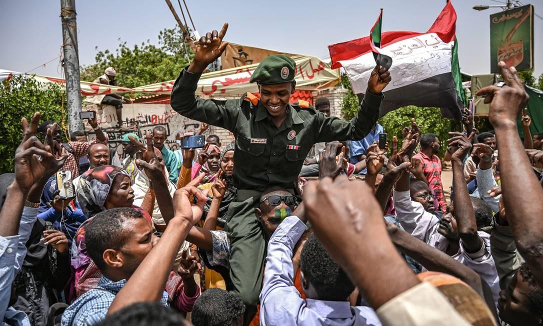 Manifestantes sudaneses gritam slogans enquanto carregam um oficial sudanês durante um protesto. Se a princípio exigiam a saída de Bashir, agora querem também a dissolução do Conselho Militar de transição que assumiu o poder e a instauração de um governo civil Foto: OZAN KOSE / AFP