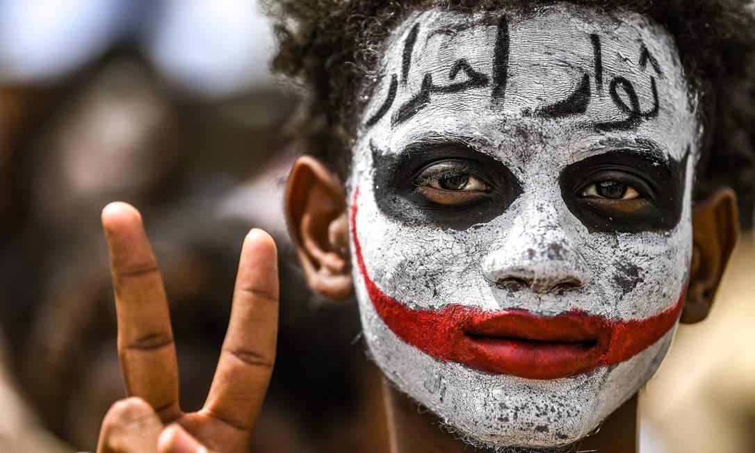 Um manifestante sudanês mostra sinal de vitória no lado de fora do complexo do Exército na capital Cartum em 18 de abril de 2019. Multidões devem convergir nesta quinta-feira na capital sudanesa, manifestantes estão determinados a completar sua revolução buscando o domínio civil. O Exército tomou o poder do presidente Omar al-Bashir há uma semana Foto: OZAN KOSE / AFP