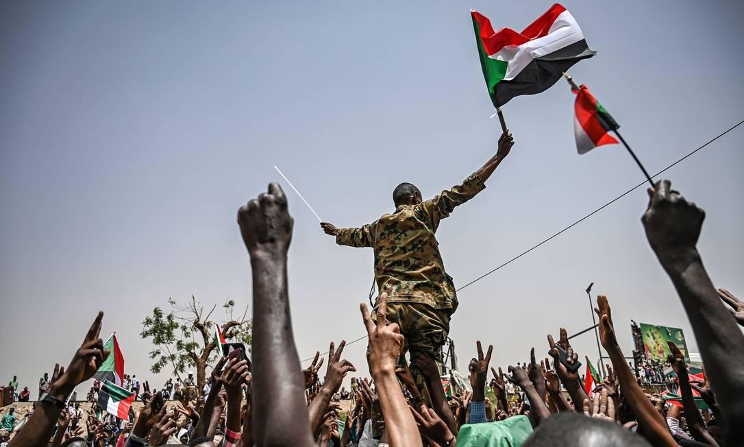 Milhares de sudaneses se reuniram pelo 13º dia consecutivo em frente ao quartel-general das Forças Armadas, situado no centro de Cartum, capital do país. Uma semana após os militares sudaneses terem retirado do poder o presidente Omar al-Bashir, protestos continuam com intuito de derrubar todo o governo Foto: OZAN KOSE / AFP