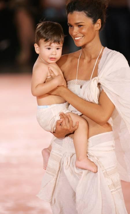 No desfile de verão 2006 da Rosa Chá, Carol Ribeiro riscou a passarela com seu filho João nos braços Foto: Randy Brooke / WireImage