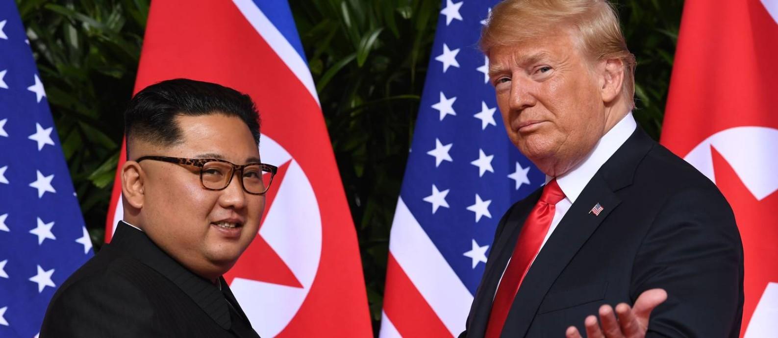 Líder norte-coreano, Kim Jong-un, e presidente dos EUA, Donald Trump, se cumprimentam no seu primeiro encontro frente a frente, realizado em 12 de junho de 2018 e Cingapura Foto: SAUL LOEB / AFP