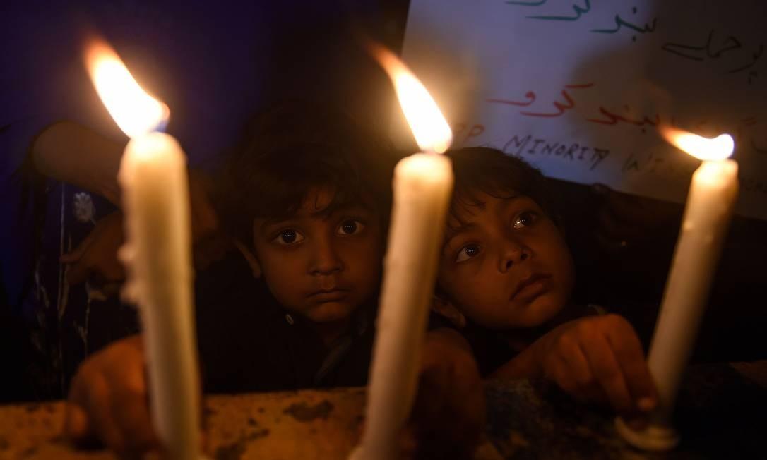 Crianças cristãs paquistanesas acendem velas em tributo às vítimas dos atentados contra igrejas católicas no Sri Lanka Foto: RIZWAN TABASSUM / AFP