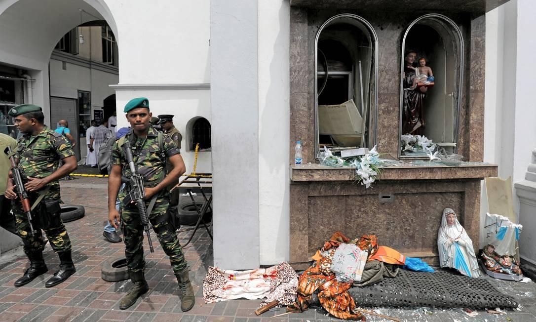 Militares de guarda ao lado de estátua da Virgem Maria destruída durante atentados no Sri Lanka Foto: DINUKA LIYANAWATTE / REUTERS