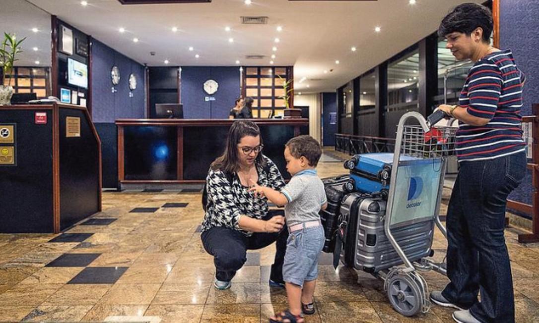 Tatiana de Jesus, Carla Braga (em pé) e o pequeno Arthur, de 2 anos: família se hospedou em hotel no Terminal 1 do Galeão para não ter que passar de madrugada pela Linha Vermelha Foto: Guito Moreto / Agência O GLOBO