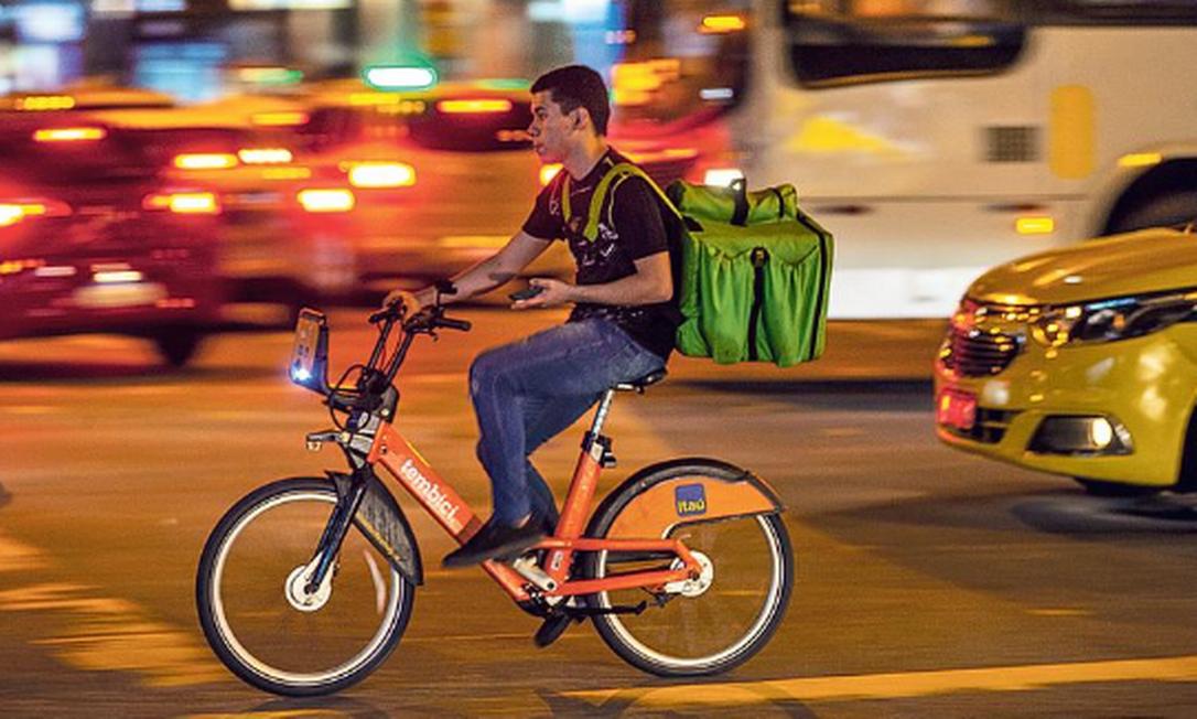Laranjinhas para muitos fins. Entregador faz delivery de restaurante no Centro usando uma bicicleta do Bike Rio Foto: Agência O GLOBO
