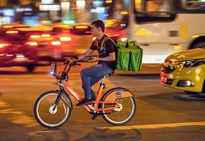Laranjinhas para muitos fins. Entregador faz delivery de restaurante no Centro usando uma bicicleta do Bike Rio Foto: Alexandre Cassiano / Agência O GLOBO