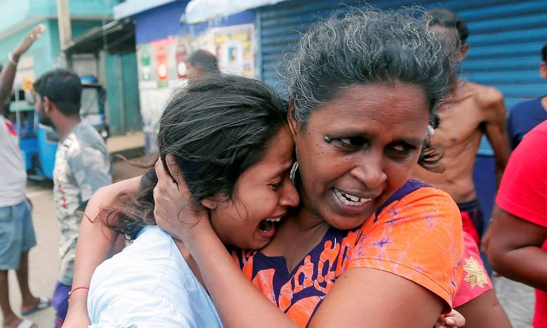 Mulheres que moram perto de igreja atacada no Sri Lanka deixam suas casas durante operação militar em veículo suspeito antes que ele explodisse em Colombo Foto: DINUKA LIYANAWATTE / REUTERS