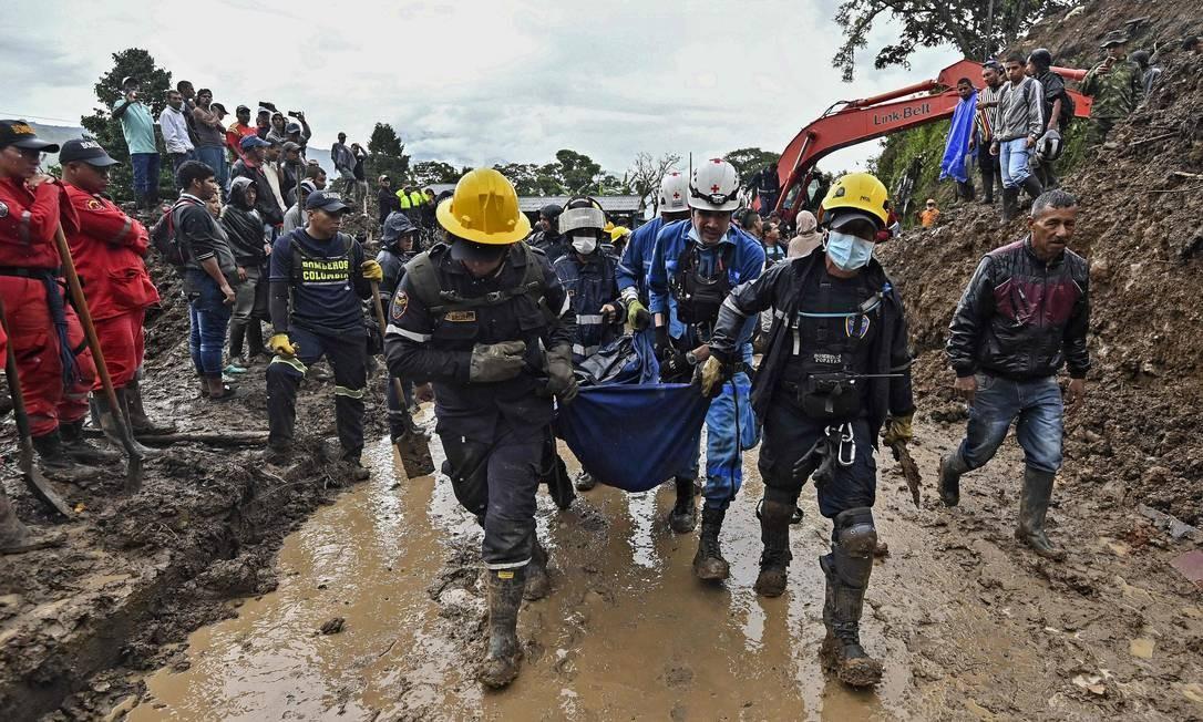 Equipes de resgate carregam o corpo de uma vítima de um deslizamento de terra em Rosas, departamento de Valle del Cauca, no sudoeste da Colômbia. Pelo menos 14 pessoas morreram e outras cinco ficaram feridas no desastre Foto: LUIS ROBAYO / AFP
