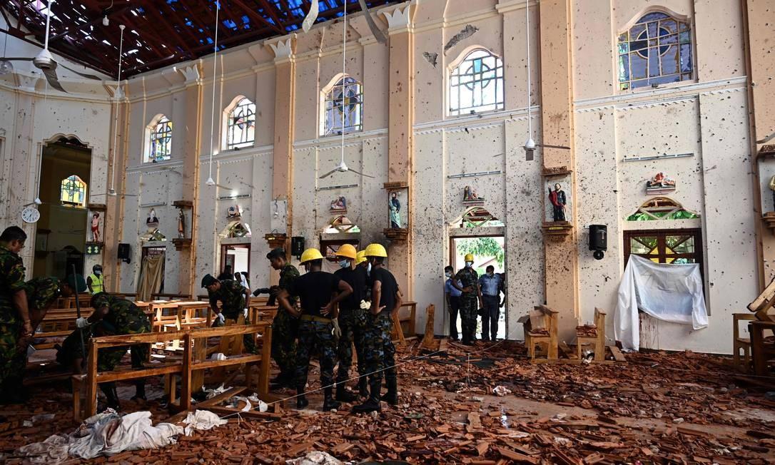Agentes de segurança inspecionam o interior da Igreja de São Sebastião, em Negombo, um dia depois de a igreja ter sido atingida por uma série de explosões de bombas contra igrejas e hotéis de luxo no Sri Lanka. Pelo menos 290 pessoas morreram na pior onda de violência que atingiu a ilha desde que a devastadora guerra civil terminou, há uma década Foto: JEWEL SAMAD / AFP