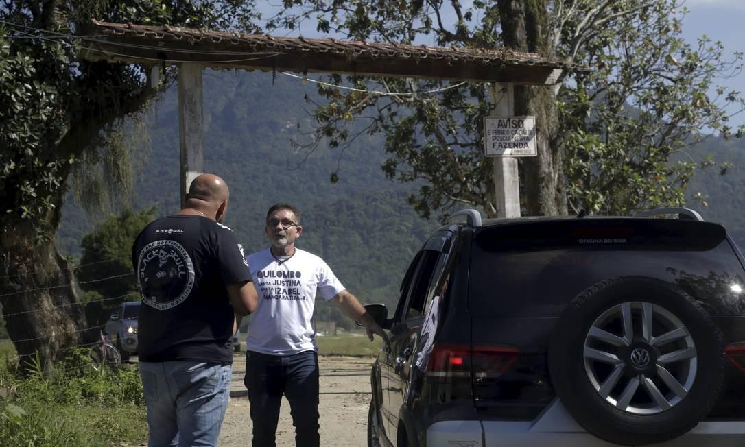 Advogado da comunidade da Estrada São João Marcos, Ivan Braga, conversa com o segurança Foto: Custódio Coimbra / Agência O Globo