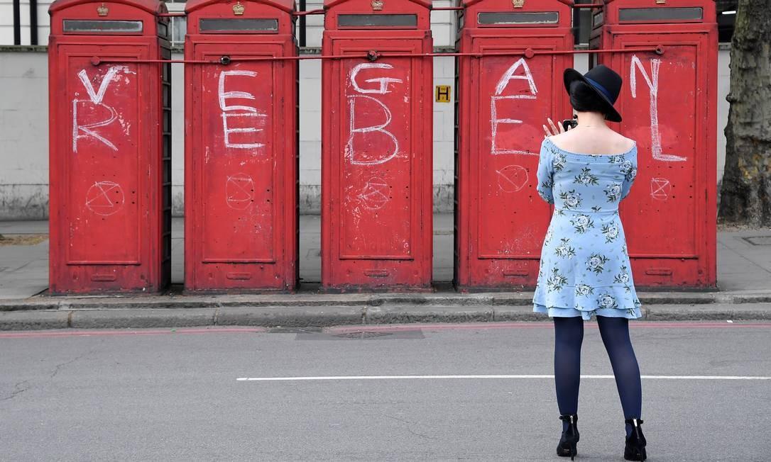 Uma mulher fotografa um slogan político em cabines de telefone durante o protesto da Rebelião da Extinção, no Arco de Mármore, em Londres Foto: TOBY MELVILLE / REUTERS
