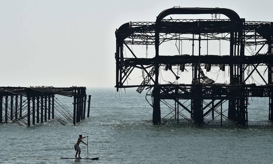 Um praticante de stand up paddle rema prósimo ao abandonado West Pier, em Brighton, no sul da Inglaterra, Foto: GLYN KIRK / AFP