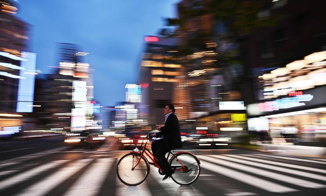 Um homem anda de bicicleta na noite de Tóquio, Japão Foto: CHARLY TRIBALLEAU / AFP