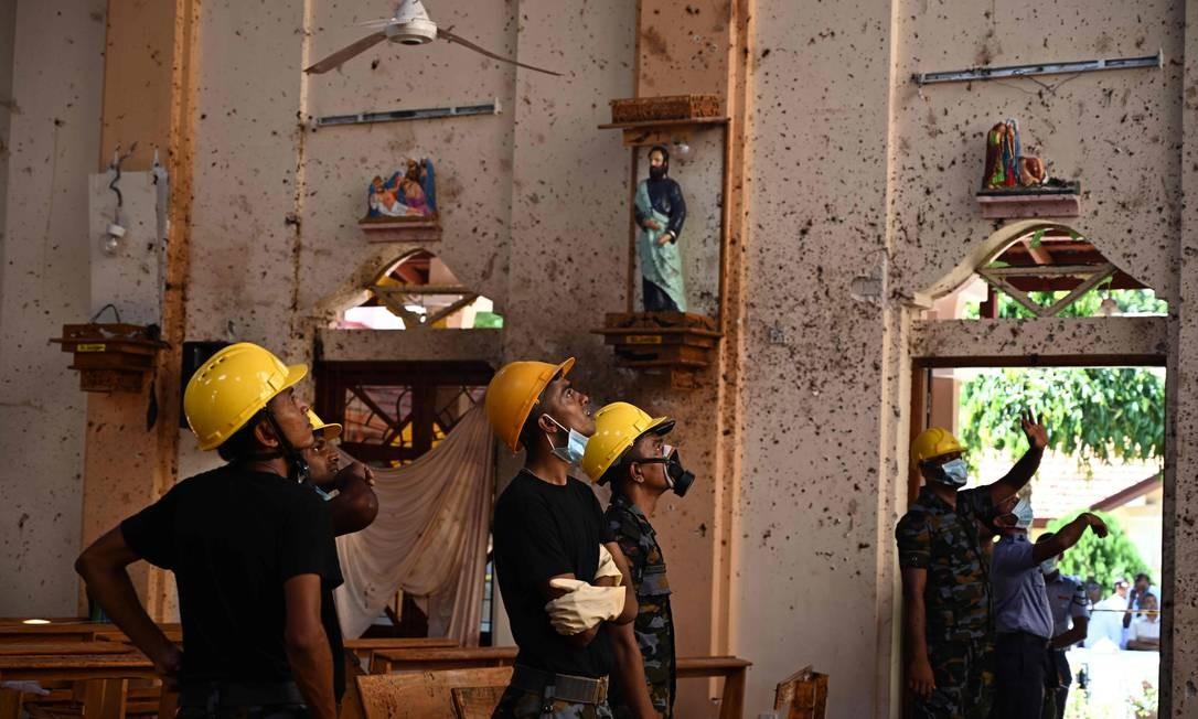 Agentes de segurança inspecionam o interior da igreja de São Sebastião, em Negombo, um dia depois de o templo ter sido atingido por uma bomba. Três igrejas católicas e quatro hotéis no Sri Lanka foram alvo de ataques coordenados no domingo. Esta é considerada a maior onda de violência desde o fim da guerra civil há uma década Foto: JEWEL SAMAD / AFP