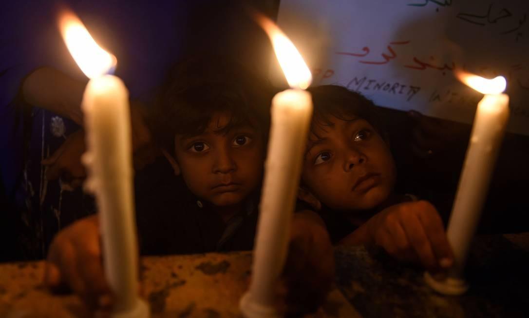 Crianças cristãs paquistanesas acendem velas para homenagear as vítimas de explosões no Sri Lanka Foto: RIZWAN TABASSUM / AFP