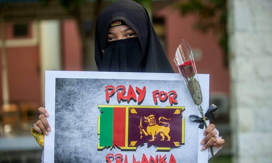 Uma estudante muçulmana da Indonésia manifesta sua solidariedade às vítimas dos atentados. O governo suspeita de um grupo islâmico até então pouco conhecido, o Thowheed Jamath Nacional Foto: JUNI KRISWANTO / AFP