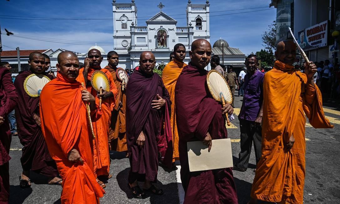 Monges budistas deixam o Santuário de Santo Antônio, em Colombo, logo após os ataques no domingo de Páscoa. Governo investiga ligações do Thowheed Jamath Nacional com grupos internacionais Foto: MOHD RASFAN / AFP