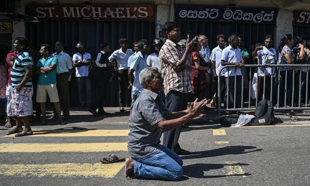 Pessoas rezam na Igreja de São Sebastião, em Negombo, um dia depois de o prédio ter sido atingido pelos atentados coordenados no Sri Lanka no domingo de Páscoa. Entre as vítimas estão estrangeiros como espanhóis, britânicos e indianos Foto: MOHD RASFAN / AFP