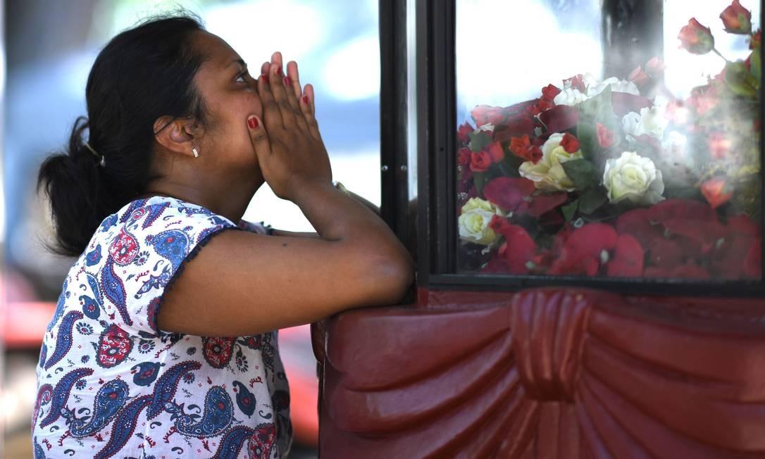 Uma mulher reza na Igreja de São Sebastião, em Negombo, um dia depois do atentado contra igrejas e hotéis Foto: JEWEL SAMAD / AFP