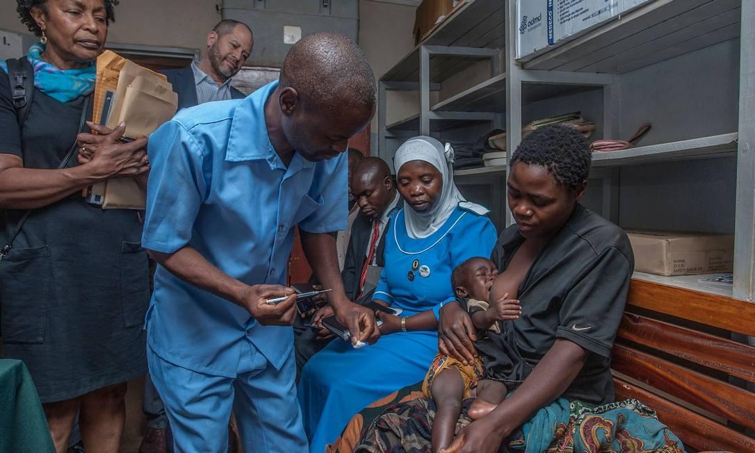 Um assistente do serviço de saúde no Malaui se prepara para aplicar a dose da vacina Foto: AMOS GUMULIRA / AFP