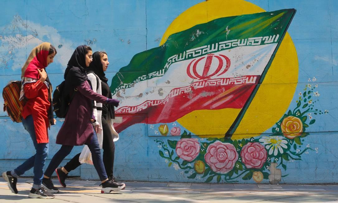 Moças caminham em frente a um mural mostrando a bandeira nacional iraniana no centro da capital, Teerã Foto: ATTA KENARE / AFP