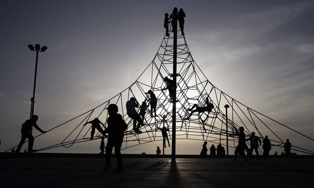 Crianças brincam em um playground na cidade litorânea israelense de Tel Aviv Foto: THOMAS COEX / AFP