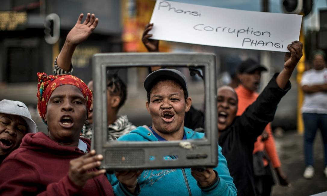 """Uma mulher segura uma faixa dizendo """"abaixo corrupção"""" em Johannesburgo, durante um protesto contra a falta de serviços de necessidades básicas Foto: MARCO LONGARI / AFP"""