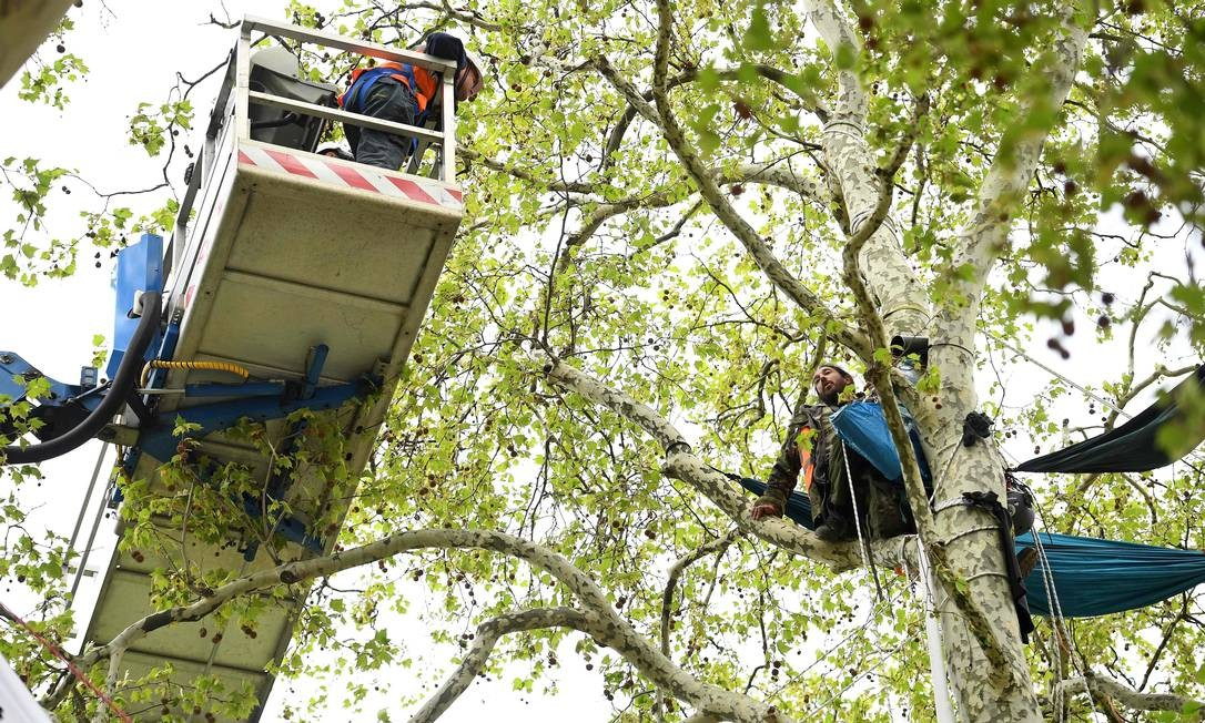 Policiais usam máquina para alcançar um ativista da mudança climática acampado no topo de uma árvore na Parliament Square, em Londres. Este é décimo dia do protesto ambiental do grupo da Rebelião da Extinção, pedindo mudanças políticas para combater a mudança climática Foto: DANIEL LEAL-OLIVAS / AFP