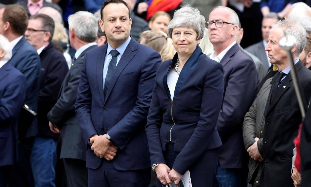 O primeiro-ministro irlandês, Leo Varadkar, e a primeira-ministra britânica, Theresa May, deixam a Catedral de Santa Ana em Belfast, após o funeral da jornalista Lyra McKee, morta durante protestos na Irlanda do Norte por um grupo dissidente do grupo terrorista Exército Republicano Irlandês (IRA) Foto: PAUL FAITH / AFP