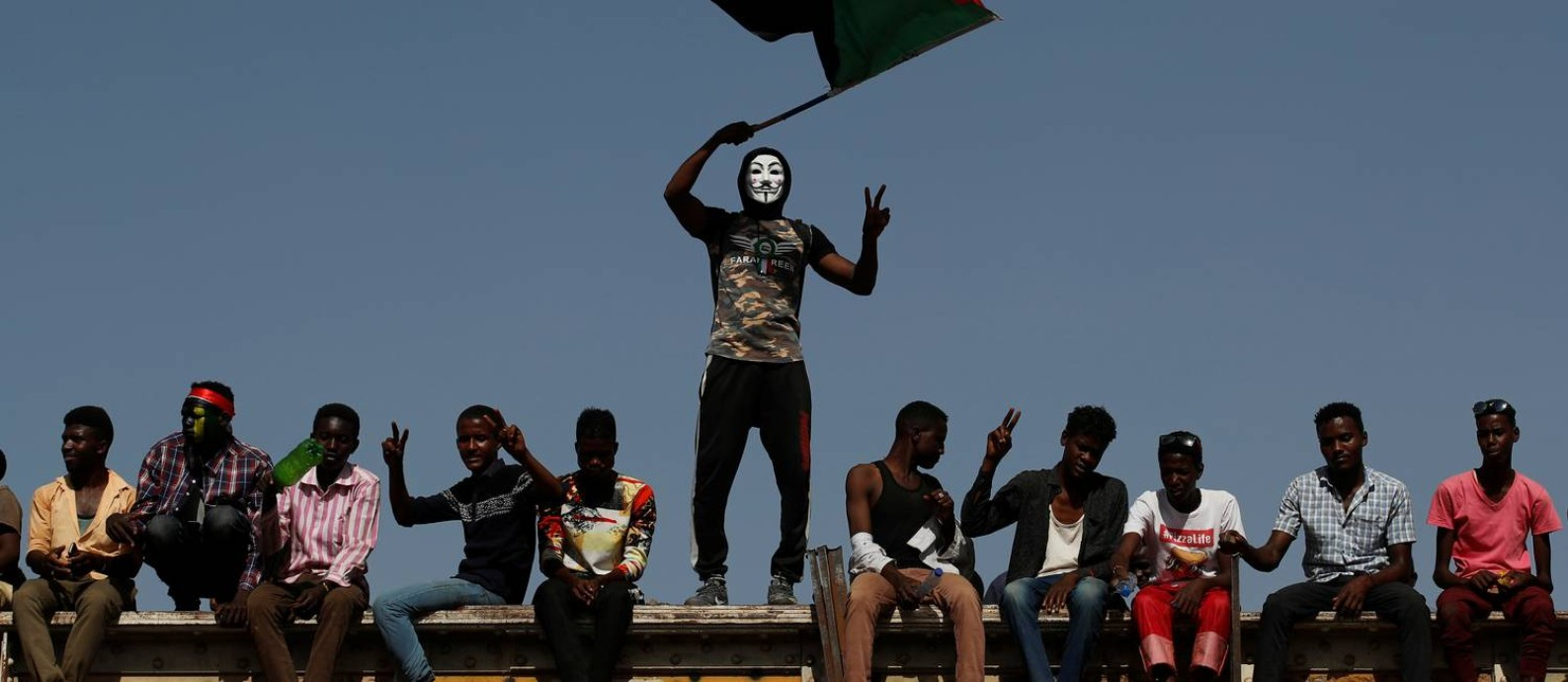 Manifestante sudanês vestindo uma máscara do revolucionário britânico Guy Fawkes balança uma bandeira do país do lado de fora do complexo do Ministério da Defesa na capital Cartum: multidão tem no entusiasmo uma marca comum Foto: UMIT BEKTAS/REUTERS