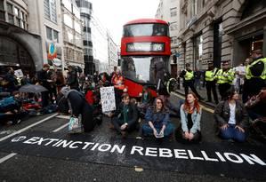 Manifestantes bloqueiam o tráfego em rua de Londres durante protesto da Extinction Rebellion nesta quinta-feira Foto: PETER NICHOLLS / REUTERS
