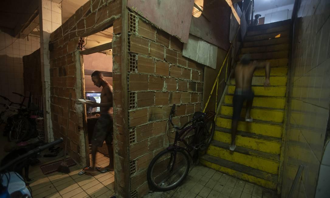 O morador Elivelton Marques na porta de sua casa com prato de comida nas mãos Foto: Alexandre Cassiano / Agência O Globo