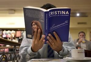 Homem segura cópia do recém-lançado livro da ex-presidente da Argentina Cristina Kirchner, 'Sinceramente': prévia da campanha Foto: JUAN MABROMATA/AFP