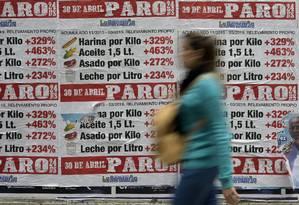 Mulher passa por cartazes feitos pelo sindicato dos bancários da Argentina mostrando a alta dos preços dos alimentos desde a posse do presidente Mauricio Macri e convocando para greve no próximo 30 de abril Foto: JUAN MABROMATA/AFP