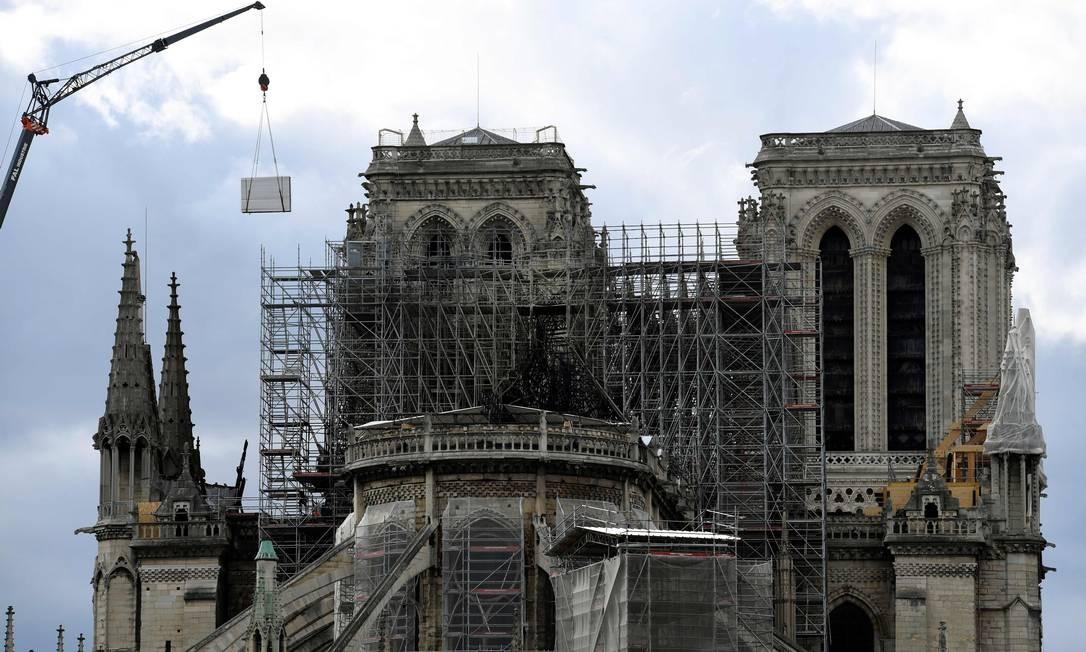Um guindaste levanta um painel como parte do trabalho de construção para proteger a Catedral de Notre-Dame de Paris Foto: BERTRAND GUAY / AFP