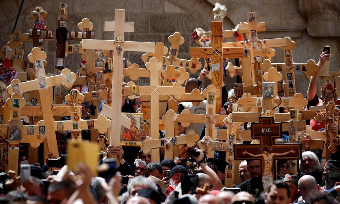 Cristãos ortodoxos se reúnem com cruzes de madeira em frente à Igreja do Santo Sepulcro enquanto celebram a Sexta-feira Santa em uma procissão na Via Dolorosa, na Cidade Antiga de Jerusalém Foto: THOMAS COEX / AFP