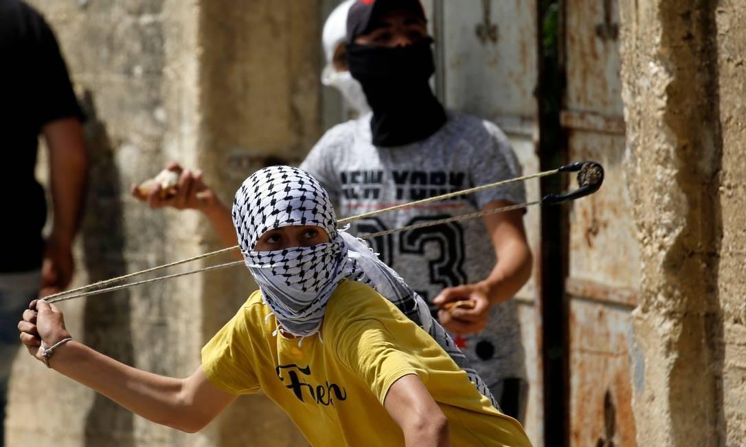Manifestante palestino se prepara para lançar uma pedra durante confrontos depois de uma manifestação contra a expropriação de terras palestinas por Israel na aldeia de Kfar Qaddum, perto de Nablus, na Cisjordânia ocupada Foto: JAAFAR ASHTIYEH / AFP